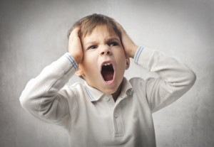 a young person with hands on the sides of their head and screaming in anger